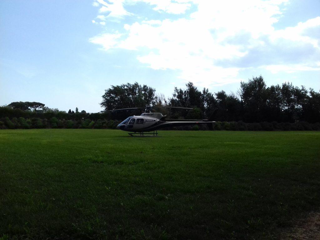 hélicoptère prêt à décoller pour emmener les mariés, grand terrain dégagé avec de l'herbe verte et ciel bleu