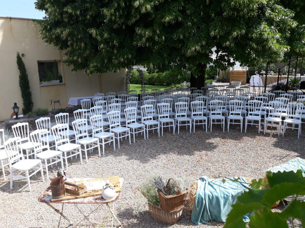 cérémonie vue surélevée, chaises alignées en arc de cercle sous l'ombre de l'arbre, bottes de paille recouvertes d'une couverture bleue