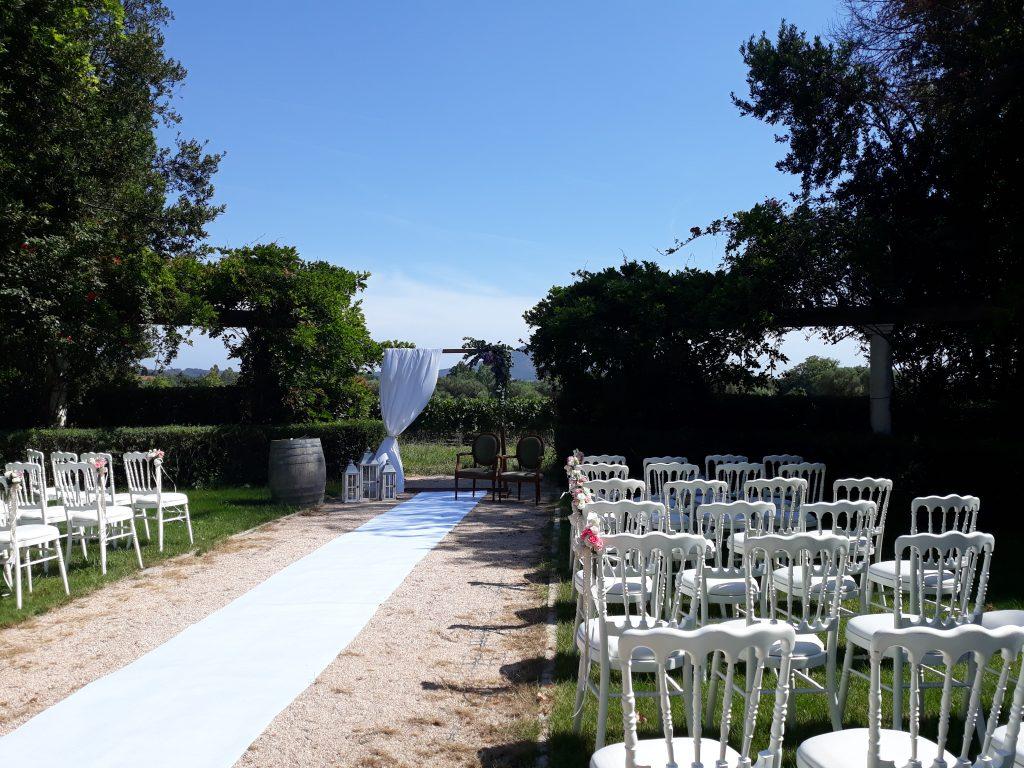 cérémonie installée de loin avec tapis blanc, chaises napoléon, domaine de la Baratonne, arche avec voile, tonneau en bois en guise de pupitre, thème épuré et naturel