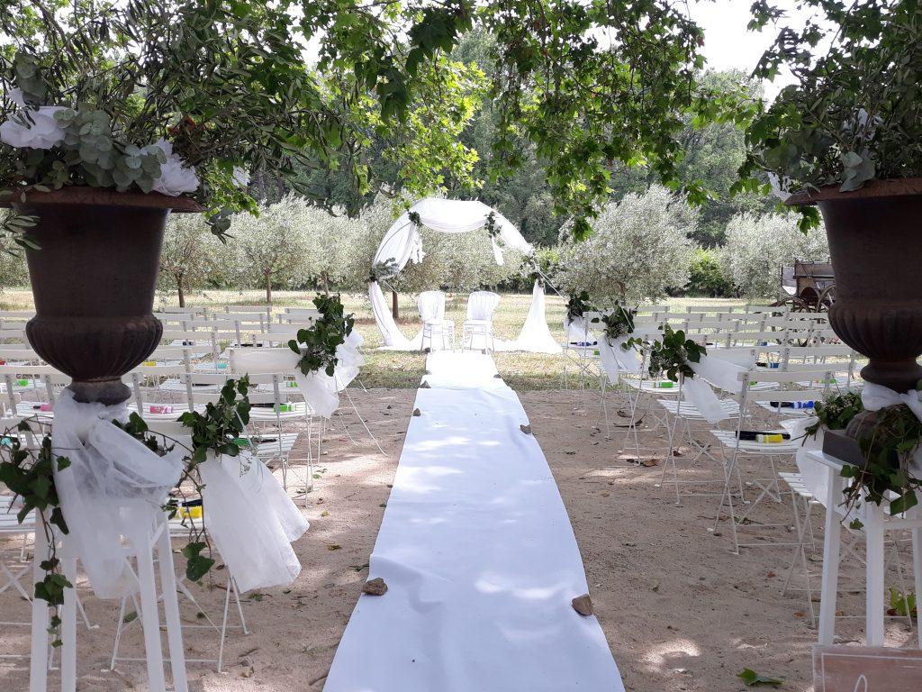 allée centrale d'une cérémonie avec l'arche au bout du tapis blanc et chaises de chaque côté