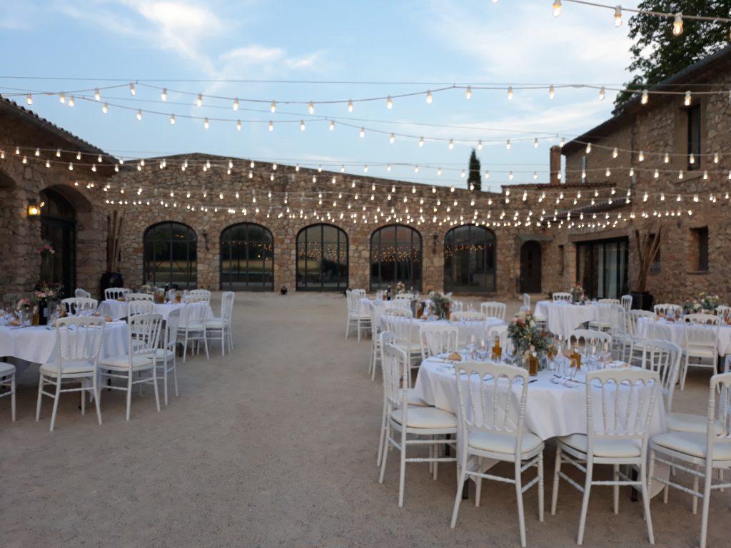 domaine LA ROTONDE espace cour avec tables dressées, guirlandes lumineuses suspendues