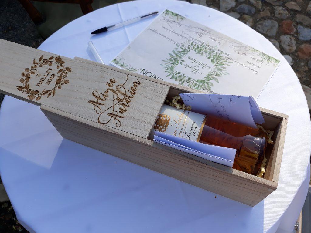 rituel de la boîte scellée, bouteille de vin rosée à l'intérieur avec discours surprises pour les mariés lors de la réouverture de la boîte après 5 ans de mariage, certificat d'union signé sur une table ronde nappée