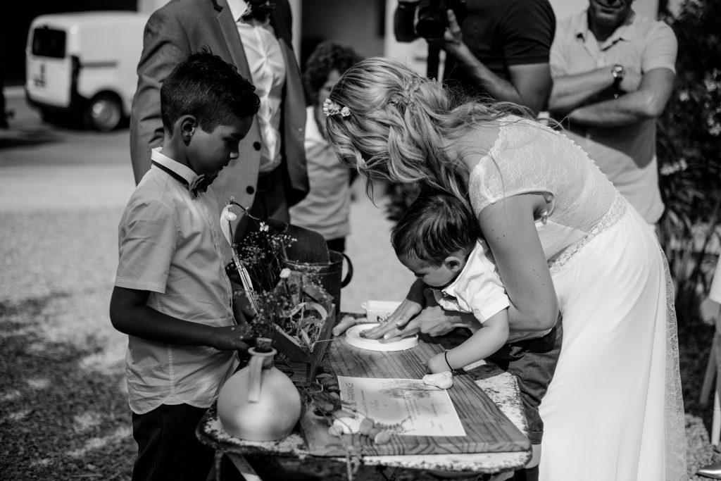 rituel des empreintes, photo en noir et blanc, l'enfant dépose sa main sur le plâtre, sa mère en mariée le porte