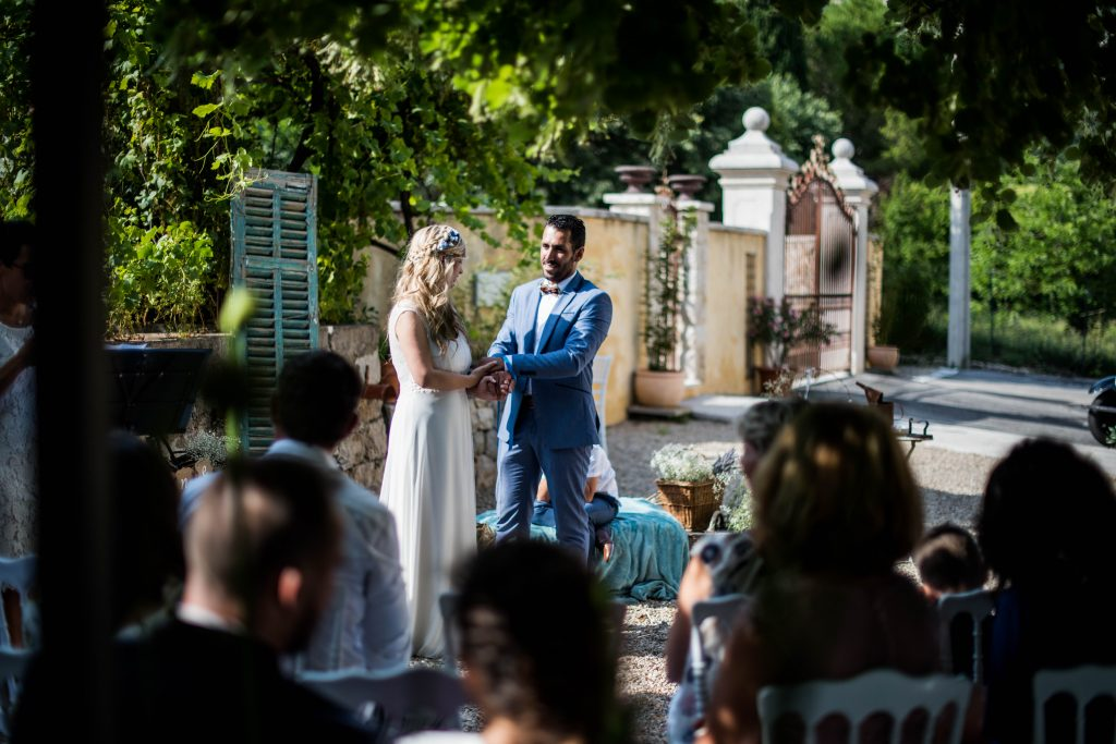 invités assis en premier plan et les mariés les bras en forme de 8 se préparent pour le rituel des rubans